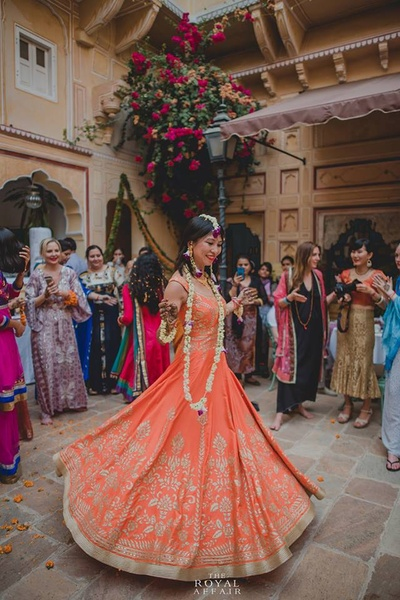 Twirling bride looking gorgeous in a saffron anarkali by Anita Dongre and floral jewellery for her mehendi ceremony held at Samode Palace, Jaipur