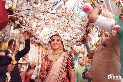Happy bride under the Floral chadar entering the wedding ceremony