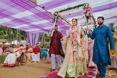 a candid capture of the bride making an entry under a phoolon ki chadaar