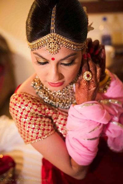 Red wedding lehenga with gold glam bridal makeup and polki studded jewellery