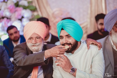 The groom's relative feeds  him a piece of mithai during a post-wedding function