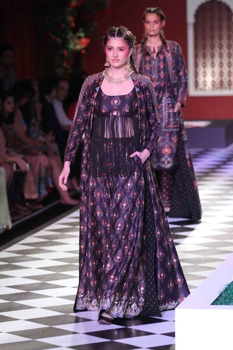 Aubergine purple and black jacket styled lehengas and dhotis with a mandrin collared jackets. Additional details of tassles and belts only upped the style quotient on these stunning outfits!