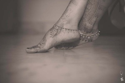 Mehendi covered feet adorned with dainty paayal featuring bead drops