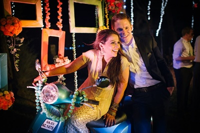 Cute picture of the bride and the groom on a scooter at their sangeet/cocktail