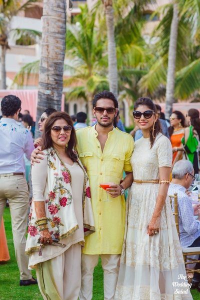 Samarth posing with her mother and sister dressed in a buttery yellow pathani and white churidaar