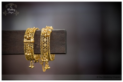 Gold intricately designed kangans with ghungru drops