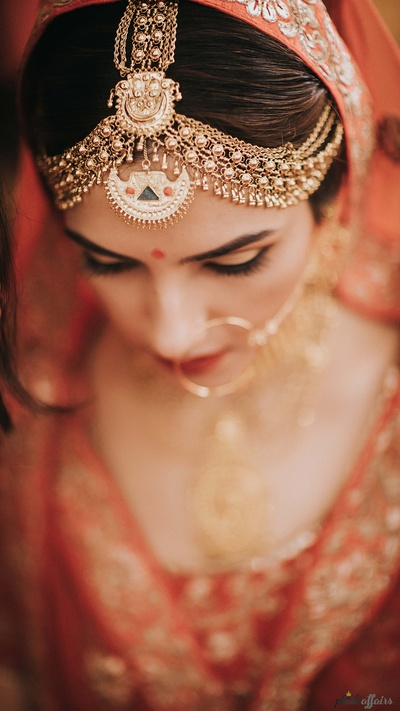 Bride's unique matha patti complementing her gold jewellery