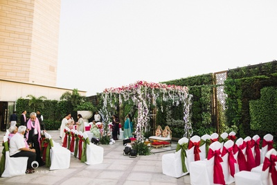 Wedding mandap beautifully decorated with white red and green flowers.