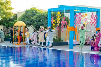 The couple and its family having a fun time along the poolside, at their mehendi ceremony.
