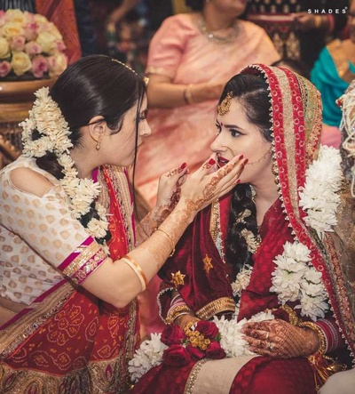 Bride in her red Sabyasachi lehenga at the wedding mandap during the ceremony
