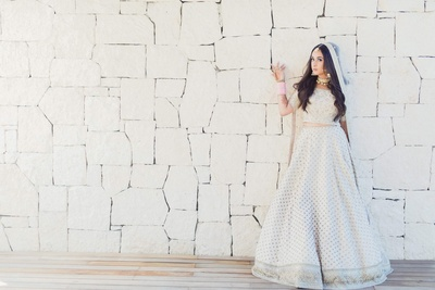 Bridal portrait of Komal in her exquisite white lehenga with silver motifs and embroidery