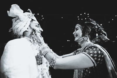 Black and white photo of the varmala between bride and groom