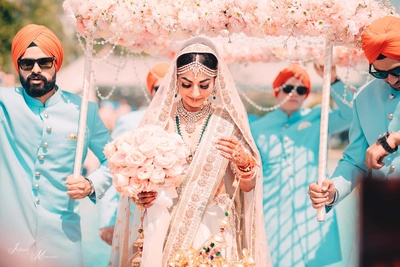 bride Simi enters the wedding mandap under her floral chaddar