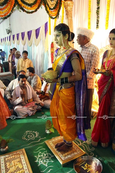 Bride performing wedding rituals covered in amber and purple silk navaari saree styled with traditional gold jewellery