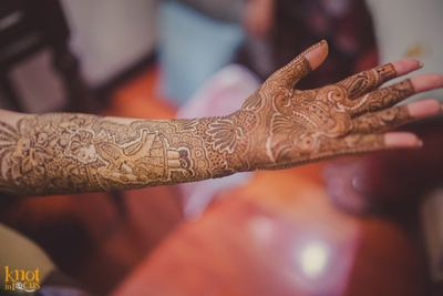 Hands covered in intricately patterned mehndi design