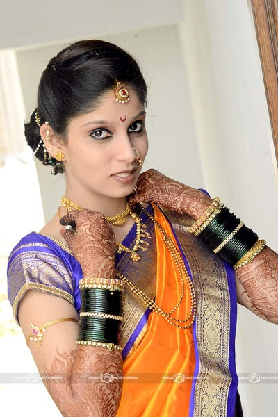 Bride decked in traditional gold wedding jewellery - Mohan mala, gold choker, armlet studded with gemstones and pearls, and a circular studded maangtikka