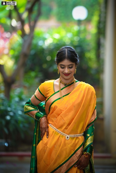 The bride flaunting her paithani saree and dainty kaamarbandh, accentuating her silhoutte.