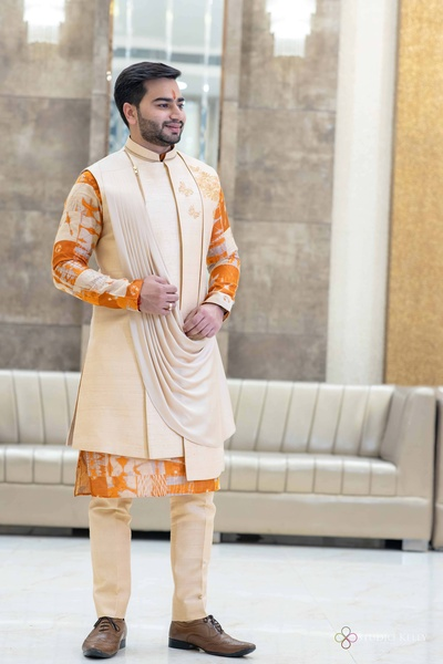 The groom donned a stunning sherwani matching his bride's attire.