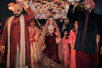 Gorgeous bride entering the wedding ceremony under the floral chadar