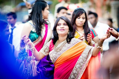 Wedding guest in a two-toned, bold bordered saree enjoying the Baraat procession