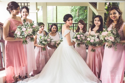 Bride posing with brides maids tn pastel colour outfits