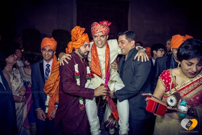 Groom dressed in off-white textured Sherwani accessorized with glistening orange silk Dushala and red Safa