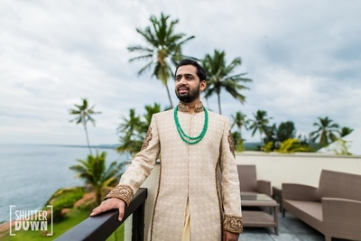 The groom in a golden sherwani and emerald necklace
