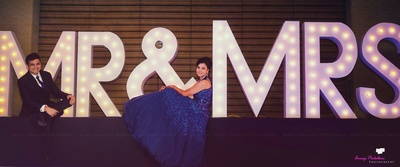 Shimmery blue cocktail ballroom gown embellished with sequins. Backdrop of fibre Mr & MRS cutout signages