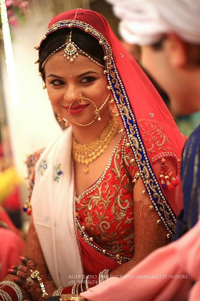 Red bridal lehenga adorned with an over-sized nath pearled nose chain, mangtikka and a dainty mathapatti
