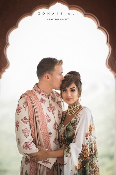 candid couple shot in their mehndi outfits