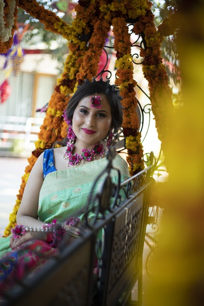 The bride looks gorgeous in this turquoise blue saree, paired with purple floral jewellery.