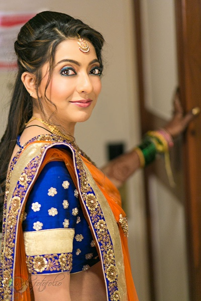Coral and blue lehenga, styled with vibrant make-up and blue eye liner
