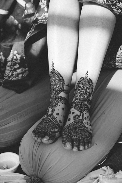 Feet decorated with intricately patterned bridal mehendi design