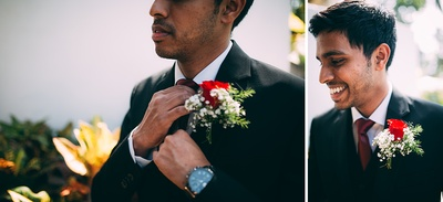 Black wedding suit styled with a white shirt and a floral corsage