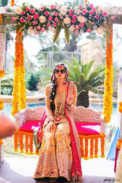Sitting on a swing decorated beautifully with colorful floral top and genda phool decor.