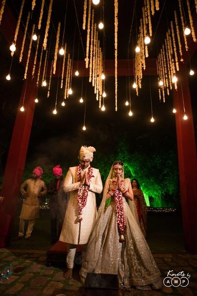 Floral wedding mandap design includes hanging lights for the night wedding
