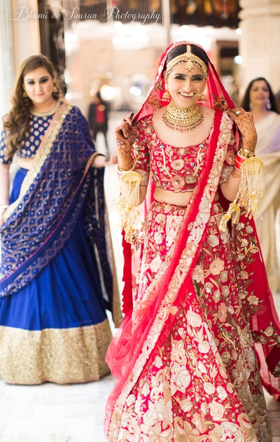 The bride looks scintillating in this red heavily embroidered lehenga and statement jewellery.
