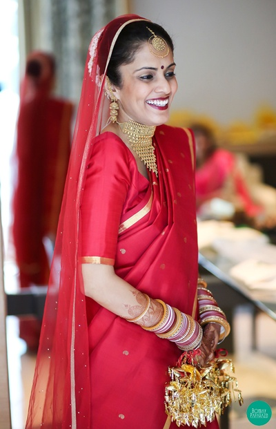 Red silk saree with gold paisley weaves and a gold border, styled with gold intricately designed choker set
