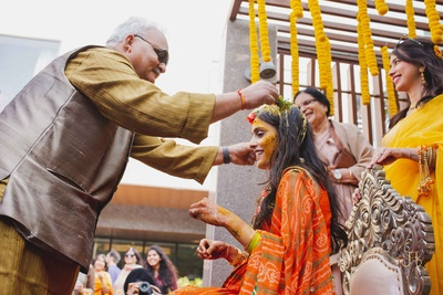 the bride's father applying haldi to the bride