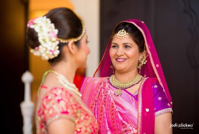 Mother of the bride dressed in a pink and purple silk saree with gold and weaves styled with polki studded jadau necklace set