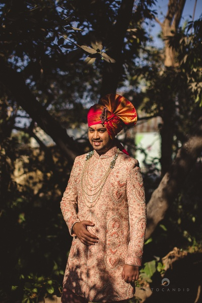 Dressed in a regal peach embroidered wedding sherwani styled with multi-strand moti haar and red embellished Safa