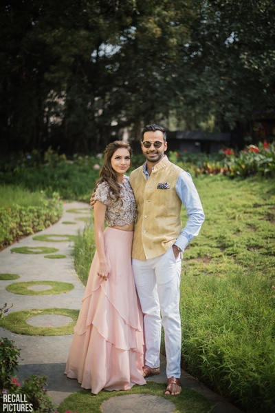 Bride in baby pink skirt paired with ivory coloured blouse posing with  the groom