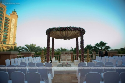 Arbor made with gold satin cloth, and pillars festooned with floral arrangement