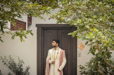 the groom in an ivory sherwani with pink dupatta