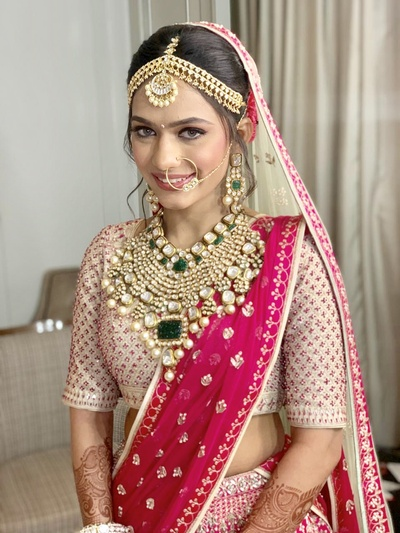 The bride looking drop, dead gorgeous in a fuschia pink lehenga by Anita Dongre with polki and emerald jewellery