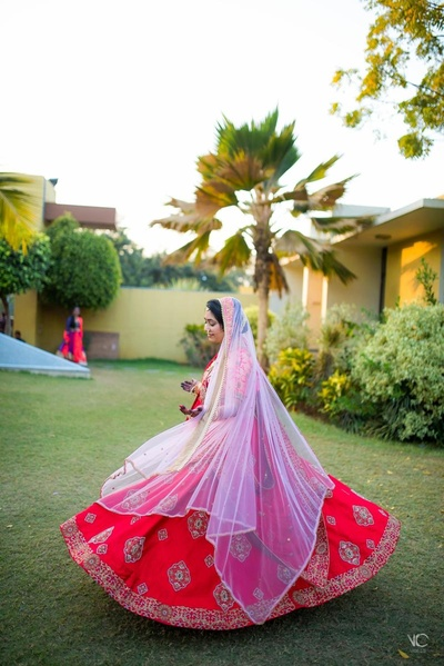 Twirling bride in this beautiful red, pink and golden bridal lehenga