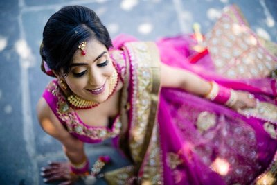 candid bridal photography in a pink lehenga