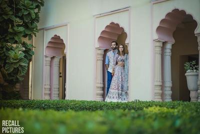 Bride in a Rahul Misra lehenga posing with her groom for their mehendi photo shoot