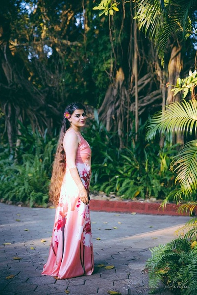 Pink satin maxi dress with floral prints and loose hair for a romantic pre wedding photo shoot