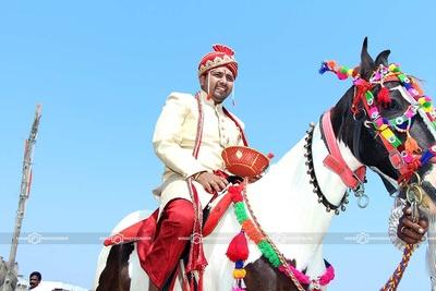 Groom dressed in off-white bandhgala Sherwani and red Dhoti